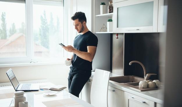 Man drinkt een kopje koffie en chatten op de telefoon