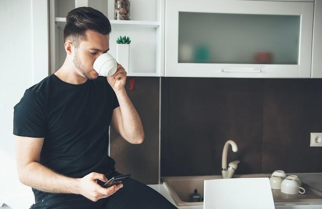 Man drinkt een kopje koffie tijdens het chatten op de telefoon