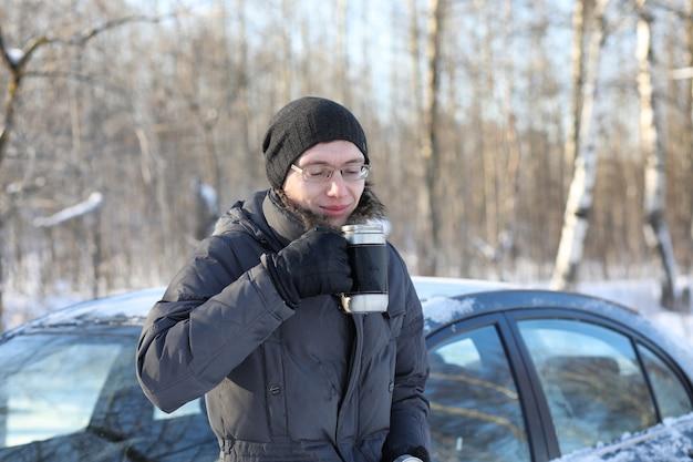 Man drinkt hete thee uit mok buiten in zonnige winterdag