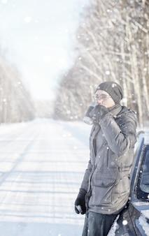 Man drinkt hete thee uit mok buiten op winterweg