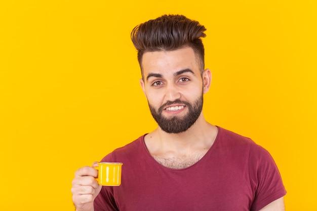 Man drinkt koffie uit kleine kop op gele muur