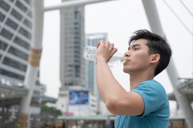 Man drinkwater na het sporten in de stad