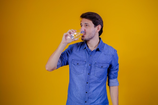 Man drinkwater op gele achtergrond.