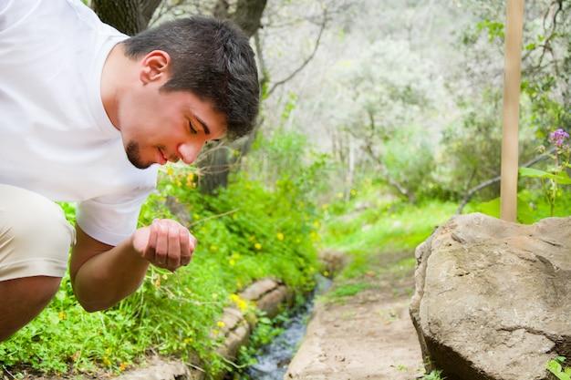 Man drinkwater uit de beek