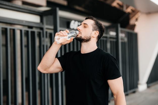 Man drinkwater uit plastic fles na het joggen met gesloten ogen. moeilijke oefening. zorg voor jezelf concept. drink meer water. sport in grote stad concept.