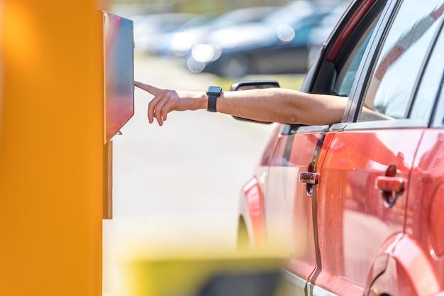 Man drukknoppen parkeermeter bij de ingang van de tolparking