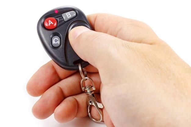 Man drukt op de knop op de afstandsbediening van de garagedeur