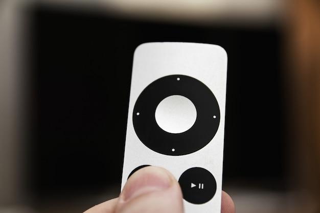 Man drukt op een knop op de moderne grijze stalen afstandsbediening op de achtergrond van de tv uitgeschakeld. de man zet de tv aan