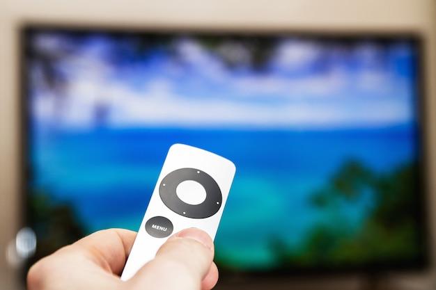 Man drukt op een knop op de moderne grijze stalen afstandsbediening op de achtergrond van de tv uitgeschakeld. een man bedient een tv