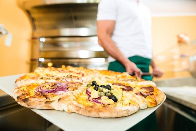 Man duwt de afgewerkte pizza uit de oven