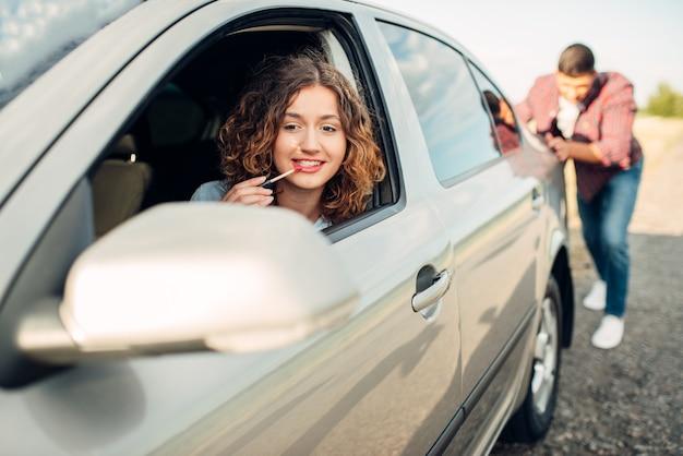 Man duwt een kapotte auto op de weg, vrouwelijke bestuurder. voertuig met problemen
