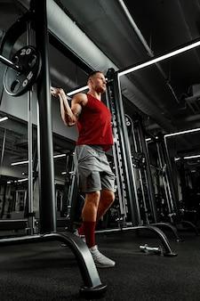 Man een atleet is bezig met een sportschool, een oefening doen op de spieren van de armen biceps zwarte achtergrond. hoge kwaliteit foto.