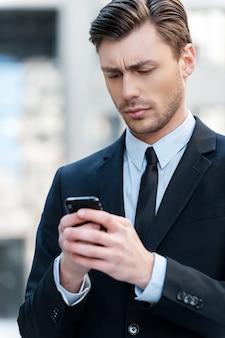 Man een bericht te typen. vrolijke jonge man die een mobiele telefoon vasthoudt en ernaar kijkt