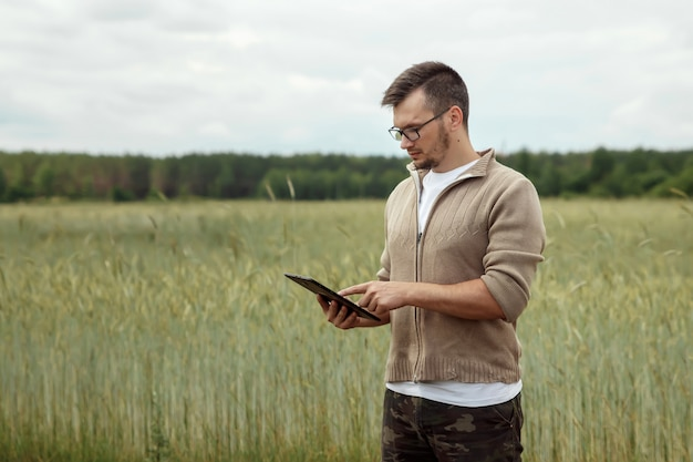 Man een boer in het veld staan en een tablet gebruiken.