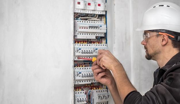 Man, een elektrotechnicus die in een schakelbord met zekeringen werkt