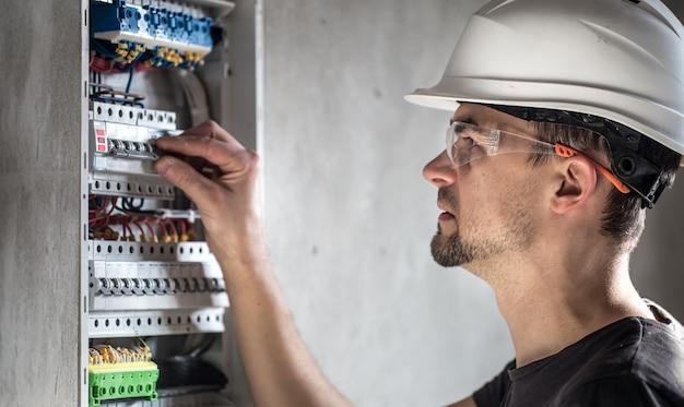 Man, een elektrotechnicus die werkt in een schakelbord met zekeringen. installatie en aansluiting van elektrische apparatuur.