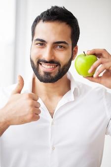 Man eet appel. mooi meisje met witte tanden bijten apple.