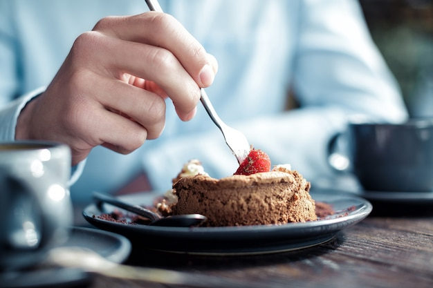 Man eet een cake met aardbeien in een café, close-up