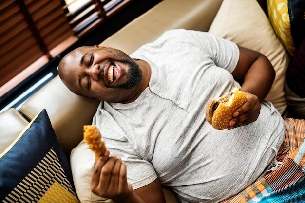 Man eet een grote hamburger