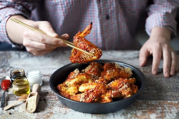 Man eet met stokjes kippenvleugels. kippenvleugels op chinese wijze met sesamzaadjes.