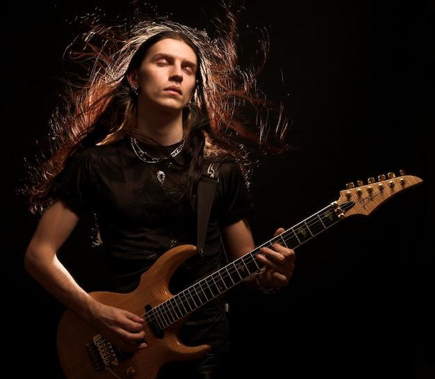 Man elektrische gitaar spelen. wind in haar.