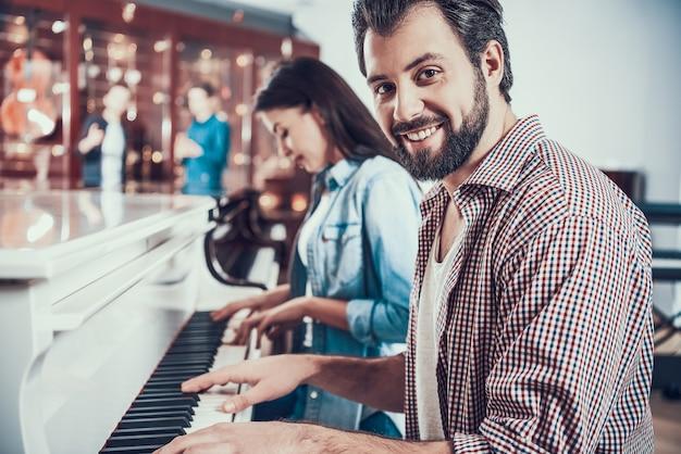 Man en aantrekkelijke vrouw spelen een piano in de winkel