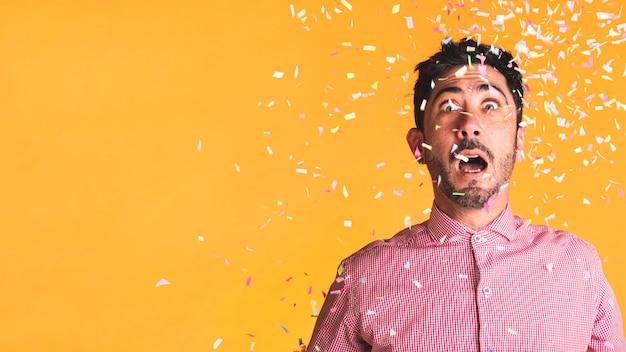 Man en confetti op oranje achtergrond met kopie ruimte