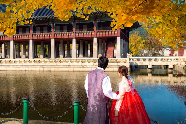 Man en dame in hanbok kleden gang in het paleis van seoel in de tuin van de ginkgoherfst