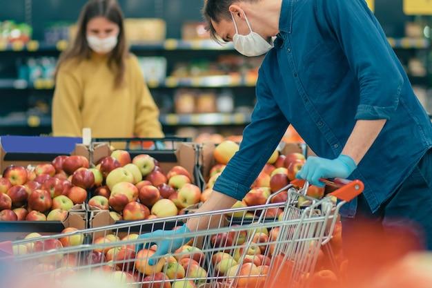 Man en een vrouw in beschermende maskers winkelen in een supermarkt