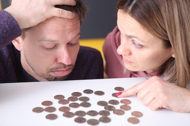 Man en een vrouw kijken boos op munten op tafel. gezinsbudget planning concept