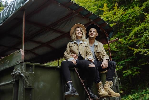 Man en een vrouw met een hoed zitten op een aanhangwagen en kijken omhoog naar de lucht