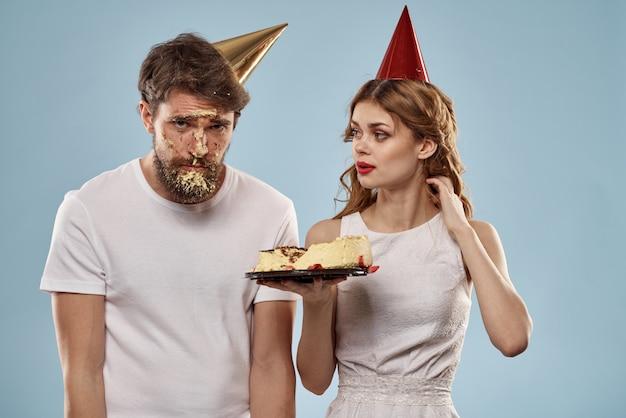 Man en een vrouw op een verjaardag met een cupcake en een kaars in een feestelijke pet veel plezier en vieren de vakantie samen, gelukkig paar