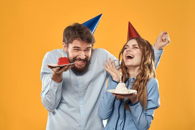 Man en een vrouw op een verjaardag met een cupcake en een kaars in een feestelijke pet veel plezier en vieren samen de vakantie