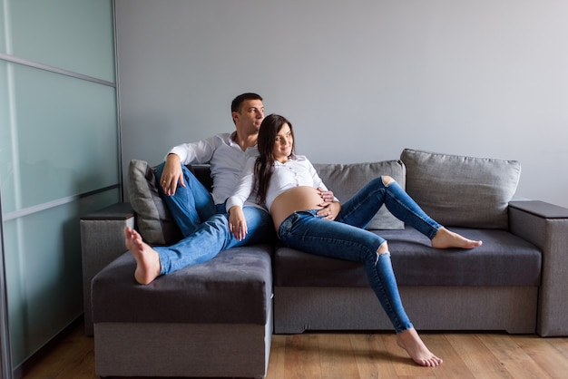 Man en een zwangere vrouw zitten knuffelen op de bank.
