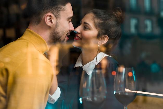 Man en glimlachende vrouw dichtbij glazen wijn in restaurant dichtbij venster