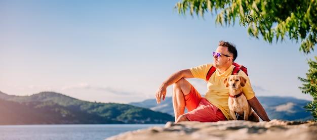 Man en hond zittend op een stenen dok en genieten van de zon