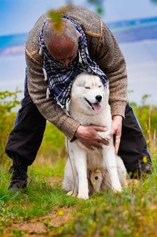 Man en husky hond wandelen in het park.