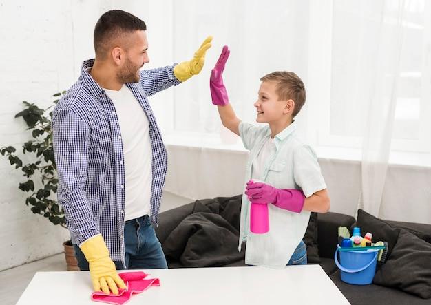 Man en jongen high-five elkaar voor het schoonmaken