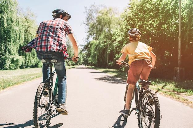 Man en kind rijden samen op de fiets op de weg