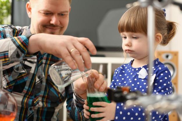 Man en klein meisje spelen met kleurrijke vloeistoffen