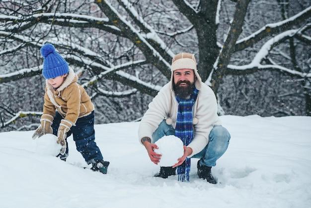 Man en kleine jongen die een sneeuwpop buiten maken