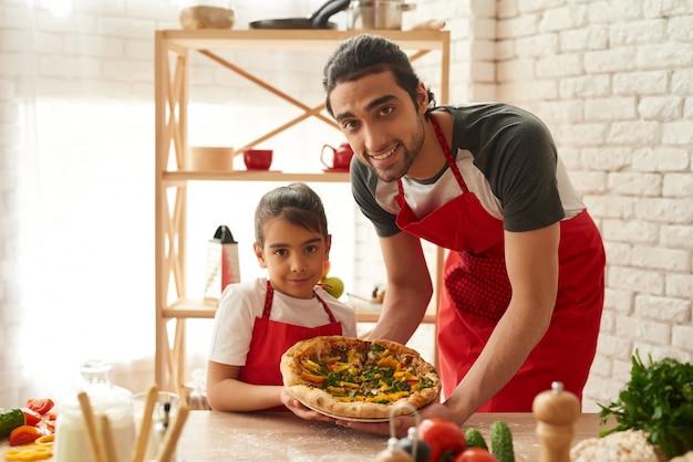 Man en meisje gekookte pizza op keuken