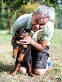 Man en puppy rottweiler voor witte achtergrond