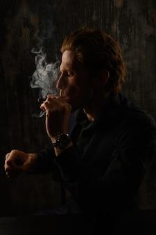 Man en roken sigaret studio portret tegen donkere achtergrond