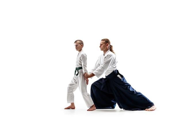 Man en tienerjongen die vechten bij aikido-opleiding in martial arts-school