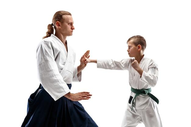 Man en tienerjongen die vechten bij aikido-opleiding in vechtsportschool. gezonde levensstijl en sportconcept. vechters in witte kimono op witte muur. karatemannen met geconcentreerde gezichten in uniform.