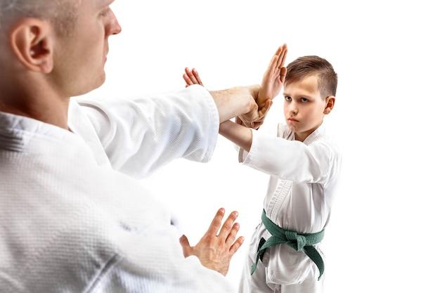 Man en tienerjongen die vechten bij aikido-training op een vechtsportschool. gezonde levensstijl en sport concept. vechters in witte kimono op witte muur. karatemannen met geconcentreerde gezichten in uniform.