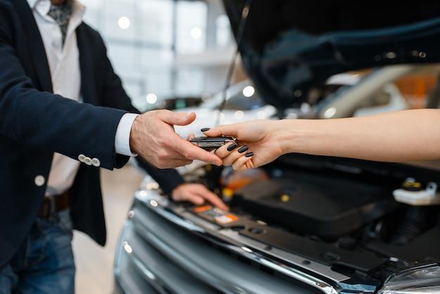 Man en verkoopster kiezen auto in autodealer. klant en verkoper in voertuigshowroom, mannelijke persoon die transport koopt, autodealerbedrijf