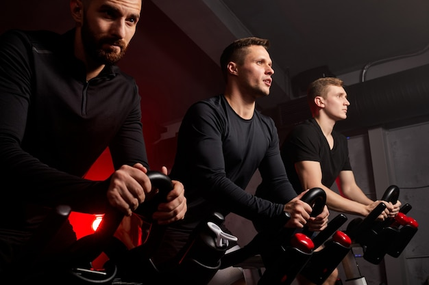 Man en vrienden op fitness fiets in sportschool tijdens training, ze kijken ernaar uit, hardwerkende sterke gespierde mannen in sportkleding