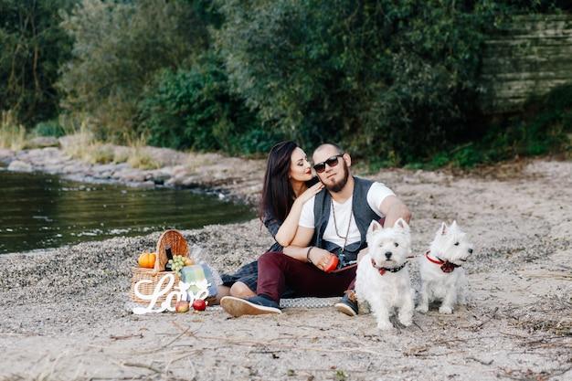 Man en vrouw amuseren zich op het strand met hun twee witte puppy's